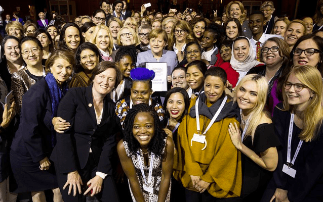 Smiling participants of eSkills4Girls project gathering around Angela Merkel.